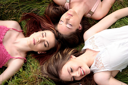 three women lying on green grass field during daytime