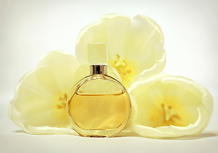 perfume spray bottle beside white flowers