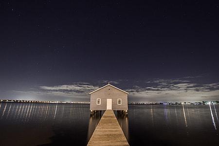 gray wooden house beside wooden dock in between body of water