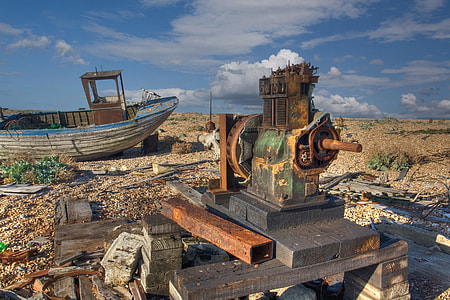 An abandoned boat and engine lie on the coast at Dungeness, Kent, England