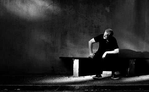 man wearing black shirt and black pants sitting on bench near wall