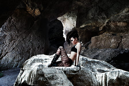 photo of woman sitting on rock in cave