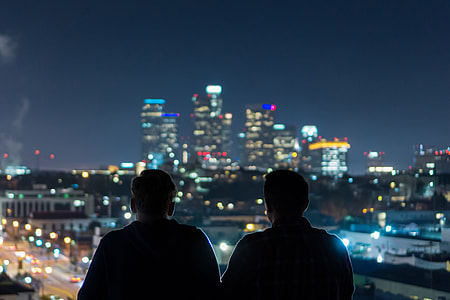Two men viewing the city at night