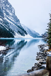 calm body of water near snow filled mountains digital wallpaper