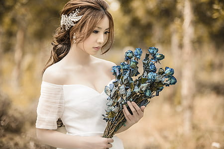 woman in white cold-shoulder dress holding blue flower bouquet