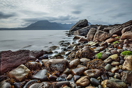 stones on seashore near mountains under cloudy sky during daytime