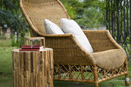 brown wicker armchair and two white throw pillows near brown leather covered book on cut log side table