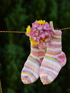 shallow focus photo of pair of multicolored socks hanging on red and yellow rope