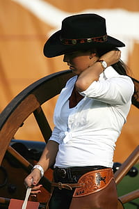 woman in white collared button-up long-sleeved dress shirt and black cowboy hat standing brown wooden frame at daytime