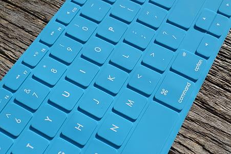 blue Apple keyboard on brown desk