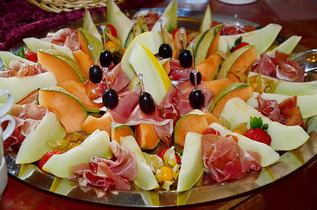 assorted sliced fruits and meat on silver platter