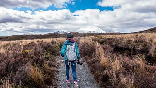 woman wearing gray travel backpack standing between brown field