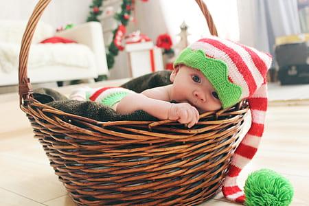infant lying on brown basket