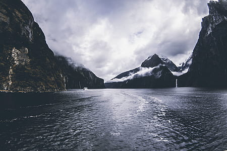 Body of Water Surround by Mountains Under Cloudy Sky