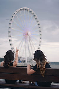 two women sitting on bench pointing on London Eye Ferris wheel