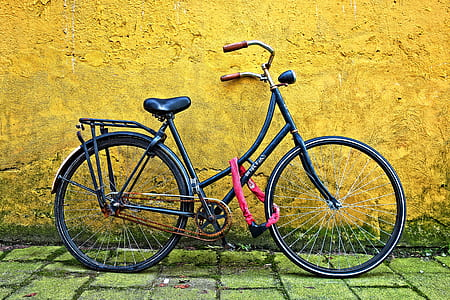 black bicycle beside yellow wall