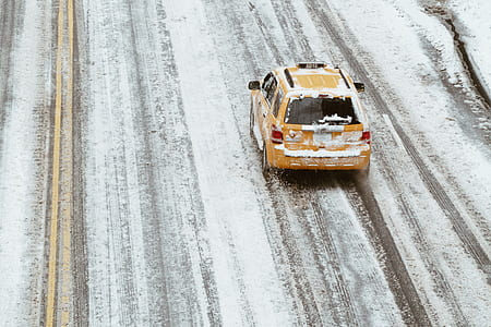 yellow taxi cab on snow filled asphalt road