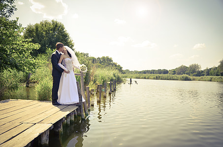 bride and groom standing on dock during daytime