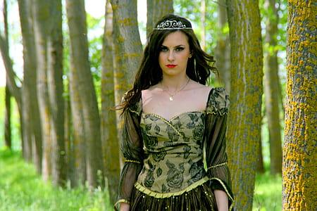 woman wearing medieval dress standing beside tree