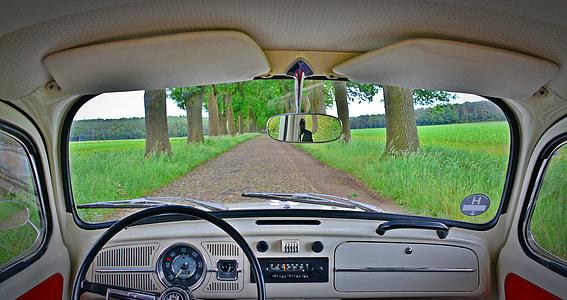 car on dirt road near grass field
