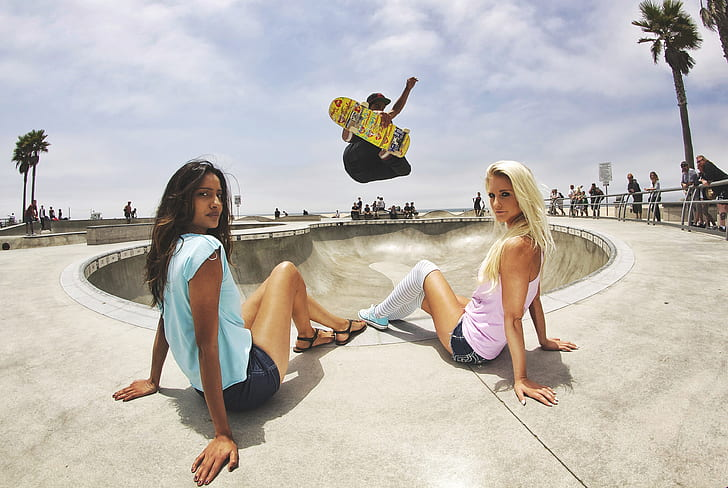 two women sitting on concrete surfave