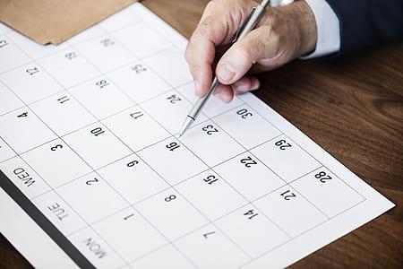person holding click pen writing on calendar