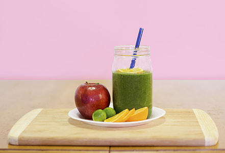 green liquid on drinking glass with assorted fruits on the plate