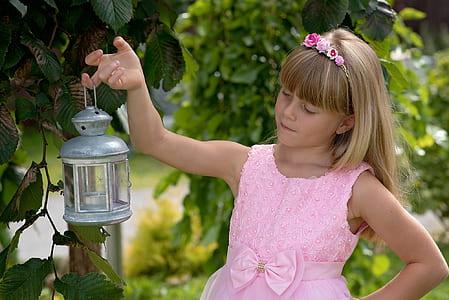 girl carrying tubular candle