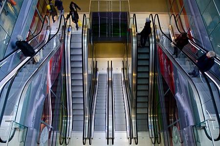 people riding on a escalator inside a buildings