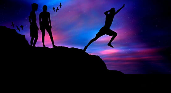 silhouette of man jumping on hill