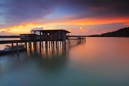 silhouette photography of sea dock on body of water
