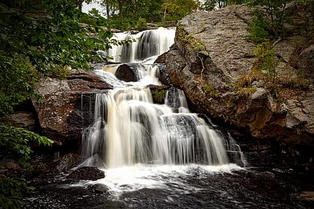 raging waterfalls beside rock formation