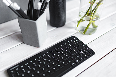 Black keyboard with pencils on a white table