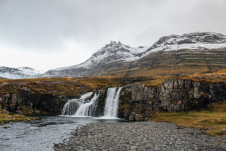 water falls on gray mountain under gray clouded sky