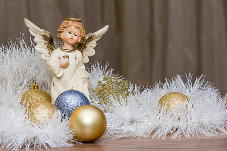 cherub figurine beside assorted-color baubles