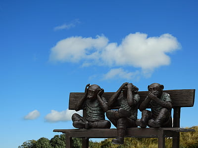 three wise monkeys sitting on bench statues