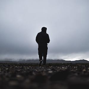 silhouette of person wearing black hoodie under cloudy sky