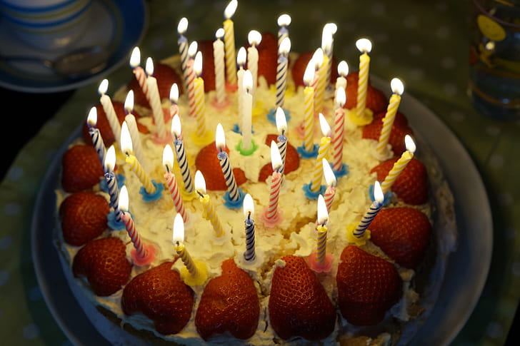 White Icing Cake With Strawberry Topping And In Lighted Candles