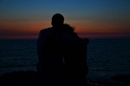silhouette of man and woman during golden hour