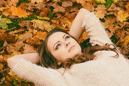 Woman in Sweater Laying on Dried Maple Leaves