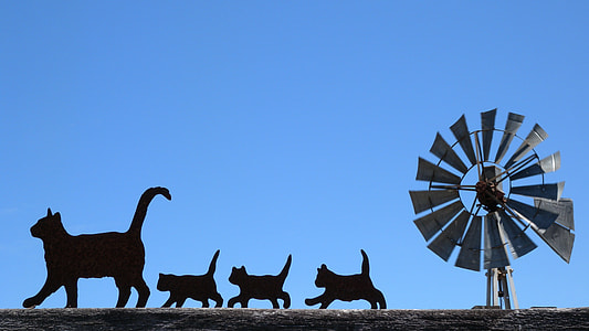 gray windmill with silhouette of cats