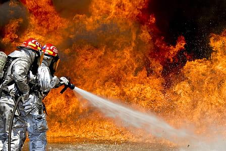 firefighters wearing silver suits spraying foam on fire