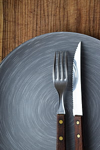 brown handled knife and fork on top of gray ceramic plate
