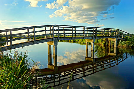 white clouds and clear blue sky reflection on river under gray and brown bridge