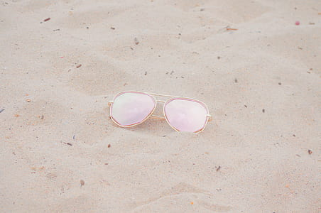 aviator sunglasses with gold frames on sand