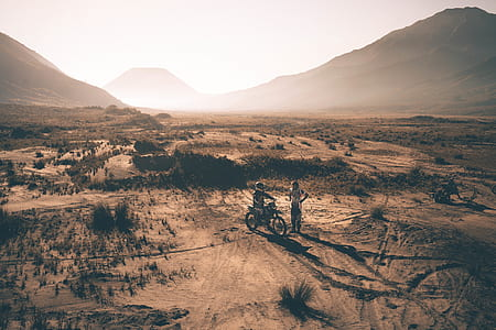 two people on desert with dirt bike photo taken during golden hour