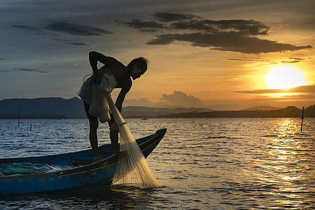 person riding row boat while holding fishing net