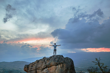 man in white shirt standing on brown rock