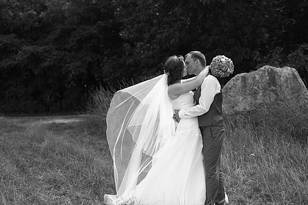 grayscale photo of newly wedding couple kissing