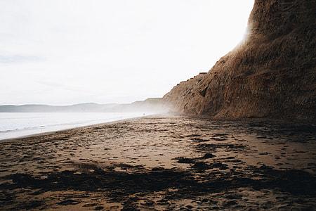 mountain cliff near body of water landscape photo